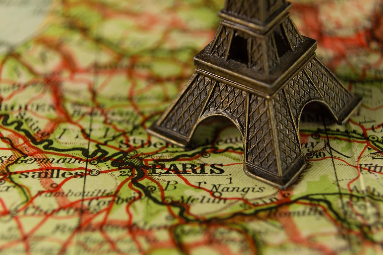 A picture of a map centered on Paris with a figurine of the Eiffel Tower