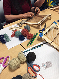 Image of patron working on loom in makerspace surrounded by yarn and other tools