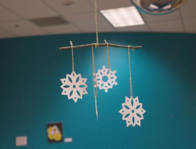 Image of paper snowflake, yarn, and stick mobile