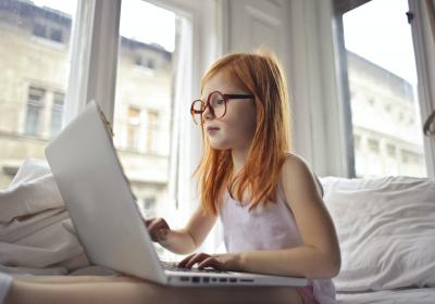 A young red-headed girl with glasses using a laptop computer.