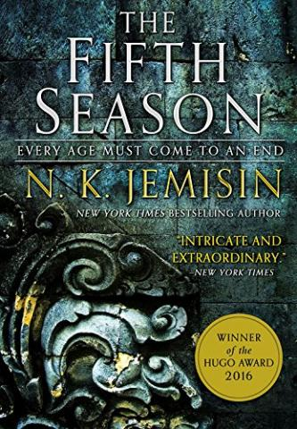 A picture of the cover, which features a closeup of a grungy, greenish blue stone wall with intricate floral carving in the corner. The Fifth Season is written in all caps.