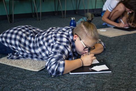 Photo of a teen wearing a flannel shirt, laying on the floor and writing in a notebook.