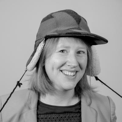 Photo of Alice B smiling at the camera wearing a hunter's cap