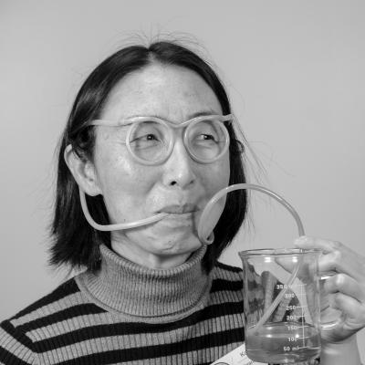 Photo of Kai Z wearing straw glasses and sipping water out of a beaker