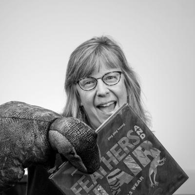 Photo of Kelly D with dinosaur puppet and book