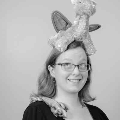 Photo of Sophia M. with a stuffed dragon on her head