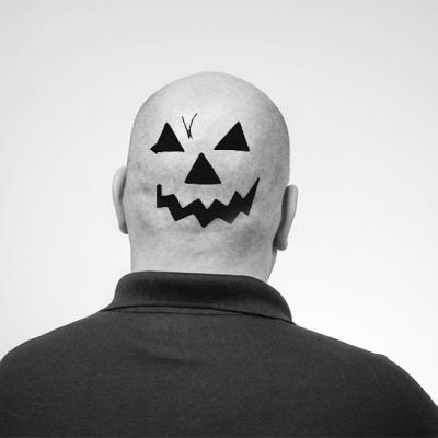 Tom F. facing away from the camera with a jack o'lantern face on the back of his head